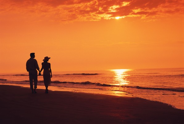 Couple Walking on Beach at Sunset