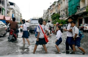 Cambodian school children walk across a flooded road in a rainy day in Phnom Penh, Cambodia, Tuesday, 29, 2008. (AP Photo/Heng Sinith)